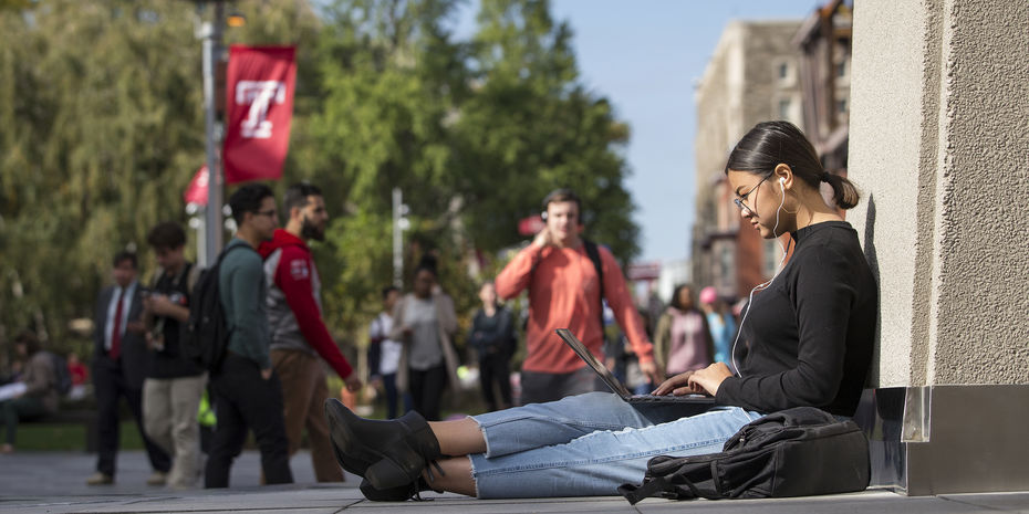 Student using laptop at bell tower on campus